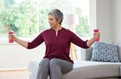 Senior woman lifting weights and working out at home. Mature woman sitting on couch doing hand stret poster