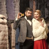 Luxury And Relationship Concept. Guy With Beard And Woman Buy Furry Coat. Couple In Love Tries Expen poster