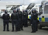 stock photo of truncheon  - Uk welsh police officers in full riot gear at the scene of a public disturbance - JPG
