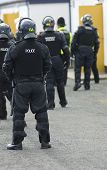 stock photo of truncheon  - Uk police officers in full riot gear at the scene of a public disturbance - JPG