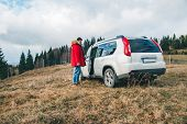 Man Sitting Down Into White Suv Car. Off Road Trip. Car Travel Concept poster