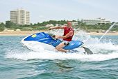 picture of jet-ski  - Young guy cruising on the atlantic ocean on a jet ski - JPG