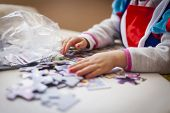 Faceless Little Girl Hand´s Playing With Puzzle Pieces Wearing A Princess Costume On A Table Full Of poster
