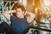 Fit Caucasian Handsome Man Sit Up On Machine In Sportswear. Young Man Sit Up Exercise To Strength Th poster