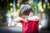 A 4 Year Old Autistic Child In A Red Shirt Closing His Ears With Hands As If Protecting From Noise.  poster