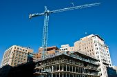 picture of construction crane  - the shell of a new city building takes shape with a beautiful deep blue sky in the background - JPG
