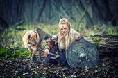 Outdoor Northern Warrior Woman With Braided Hair And War Makeup Holding Shield And Ax With Wolf Next poster