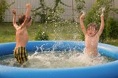 Two Boys Playing Together In Swimming Pool. Happy Children Playing In The Water. Kids Splashing The  poster