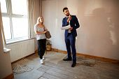 Female First Time Buyer Looking At House Survey With Realtor poster