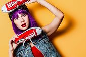 Portrait Of Young Style Hipster Girl With Purple Hair And Red Gumshoes On Yellow Background poster