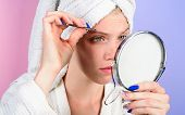 Woman Pluck Eyebrows Looking In Mirror. Epilate Eyebrows. Woman Pulls Out Eyebrows With Tweezers. Gi poster
