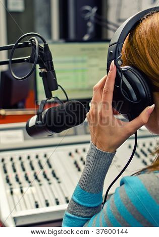 Rear View Of Female Dj Working In Front Of A Microphone On The Radio