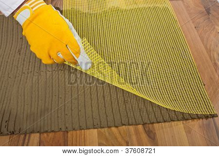 Worker Puts The Reinforced  Fiber Mesh On An Old Wooden Floor