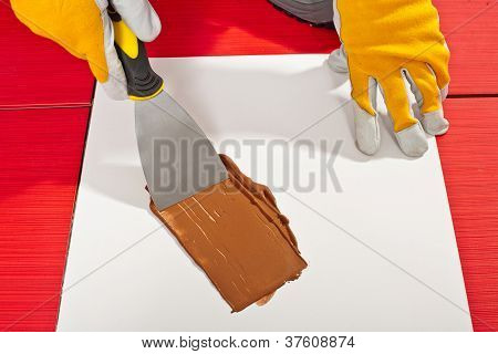 Worker With Trowel Check On White Paper Mixing Grout