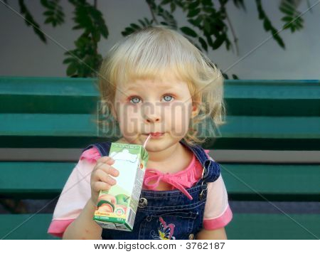 Little Girl Drinks Juice From A Tubule