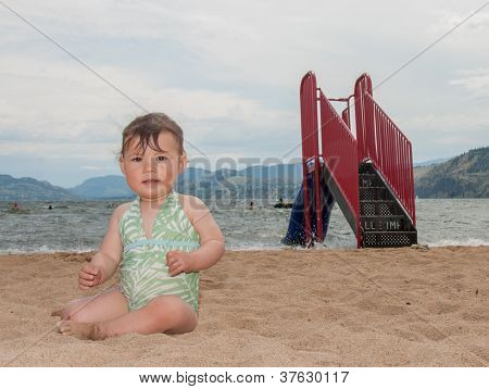 Baby Sitting On Beach In Front Of Lake