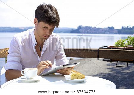 Serious Good Looking Man Working With Tablet In Front Of Lakeblet In Front Of Lake
