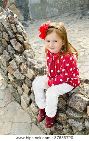 Outdoor Portrait  Of Cute Sitting Little Girl