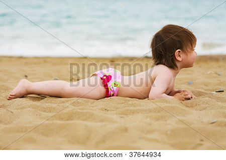 toddler girl laying on the sand beach