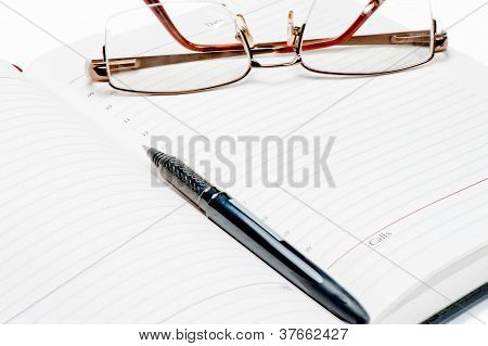 Opened diary, pen and glasses