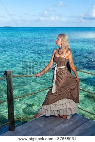 The young woman in a long sundress on a tropical beach. Polynesia. Island Tikehau.
