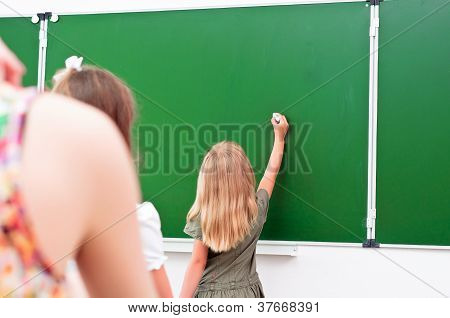 school girl writes on the blackboard