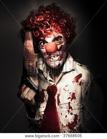 Angry Horror Clown Holding Butcher Saw In Darkness