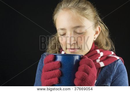 Young blond haired girl wearing winter clothing holding