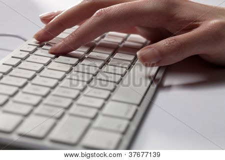 Cropped Image Of A Human Hand On Computer Keyboard