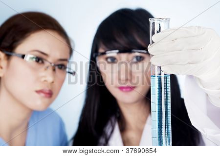 Female Scientific Research Team With Clear Blue Solution In Laboratory
