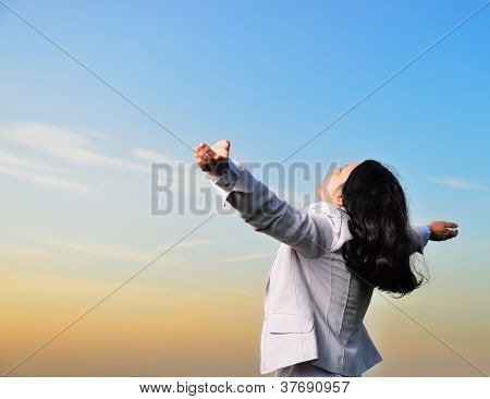 A Woman In A Business Suit With Their Hands Raised