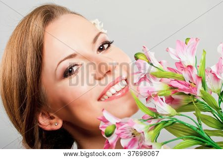 Beautiful Happy Young Woman  Holding Pink Spring Flowers