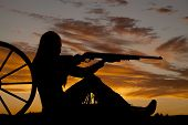 pic of wind wheel  - A woman sitting by a wagon wheel pointing her rifle  - JPG