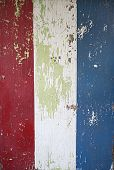 Peeled Red White and Blue Striped Background with Green Paint Showing Through