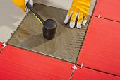 foto of mortar-joint  - worker with a rubber hammer and glass tile demonstrates how the tile adhesive work - JPG