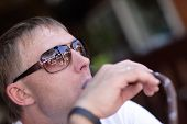 picture of shisha  - The mid adult man is smoking shisha in a cafe - JPG