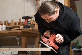 picture of work bench  - Young carpenter working in his workshop with polisher