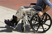 picture of crippled  - Injured man with a broken foot pushes himself along in his wheelchair - JPG
