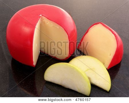 Red Skinned Swiss Cheese On Black Surface