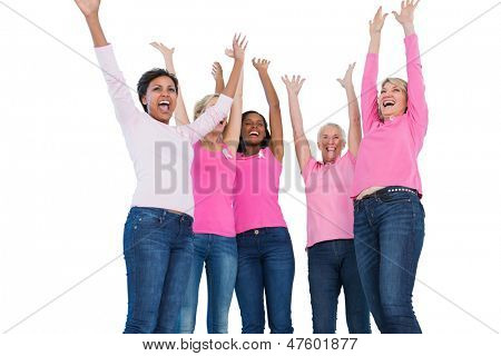 Cheering women wearing breast cancer ribbons on white background
