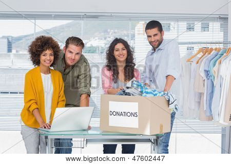 Volunteers using a laptop and taking clothes from a donation box besides hangers
