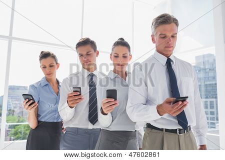 Team of business people standing together in line with their mobile in a modern office