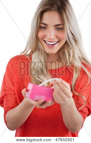 Blonde woman discovering pearl necklace in a gift box