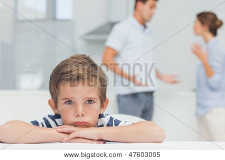 Sad boy with arms folded while parents quarreling in the kitchen