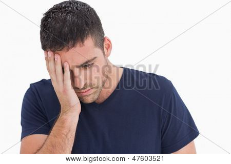 Unhappy man with head in hand on white background