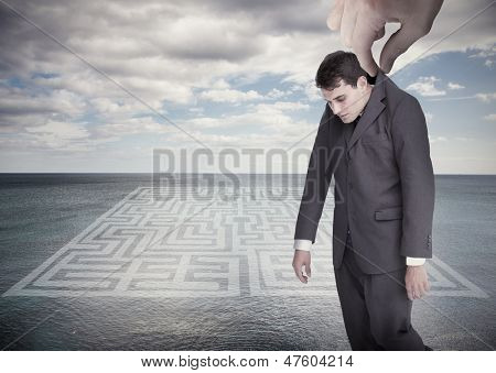 Giant hand dropping off a businessman on a surface with a labyrinth drawn on it