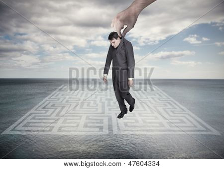 Big hand dropping off a businessman on a surface with a labyrinth drawn on it