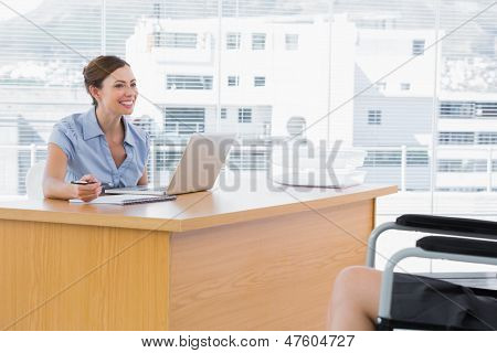 Businesswoman smiling at disabled interviewee at her desk in office