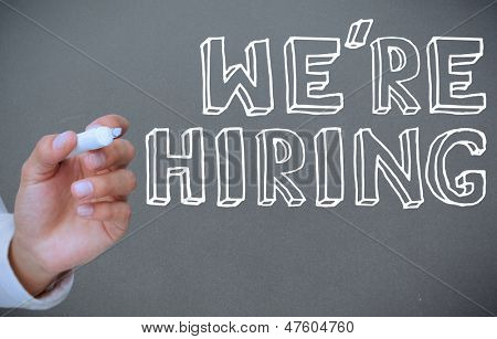Hand writing we're hiring on grey background