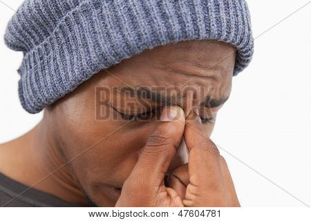 Man in beanie hat wincing with a headache on white background